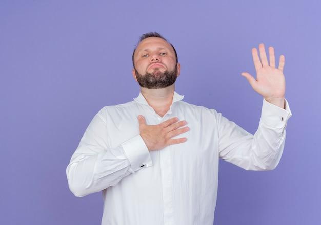 青い壁に立って自信を持って表情を誓う白いシャツを着たひげを生やした男