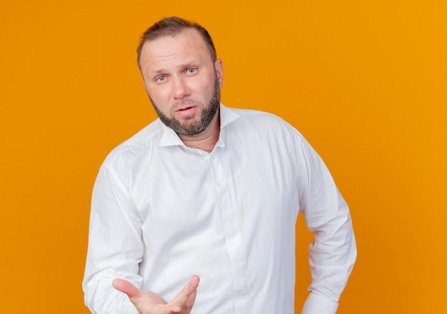 Бородатый мужчина в белой рубашке с вытянутой рукой спрашивает, стоя у оранжевой стены