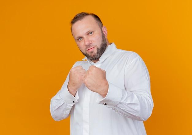 Uomo barbuto che indossa una camicia bianca con i pugni chiusi in posa come pugile in piedi sopra la parete arancione