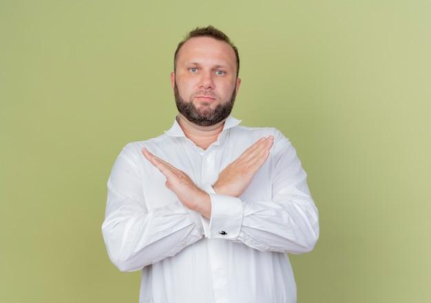 真面目な顔で白いシャツを着ているひげを生やした男は、軽い壁の上に立っている手を横切るジェスチャーを停止します