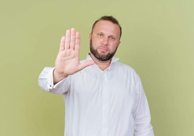 Бородатый мужчина в белой рубашке с серьезным лицом делает знак остановки с открытой рукой, стоя над светлой стеной