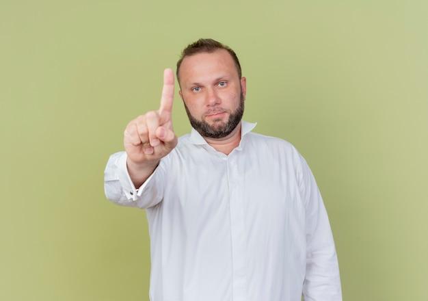 明るい壁の上に立っている人差し指の警告を示す深刻な顔で白いシャツを着ているひげを生やした男