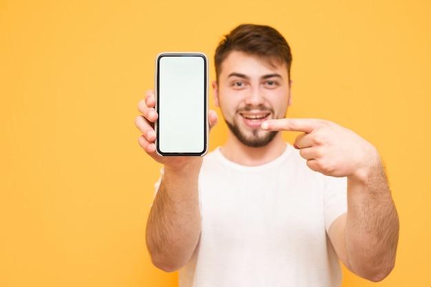 턱수염이 난 남자는 흰색 티셔츠를 입고 카메라에 흰색 화면의 스마트 폰을 보여줍니다.