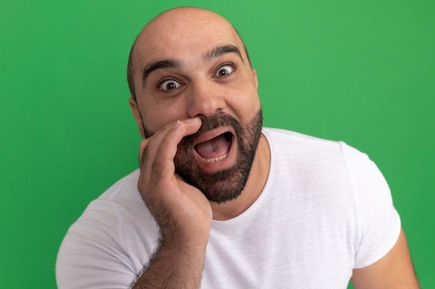 Uomo barbuto in maglietta bianca, emotivo ed eccitato che grida con la mano vicino alla bocca in piedi sopra la parete verde