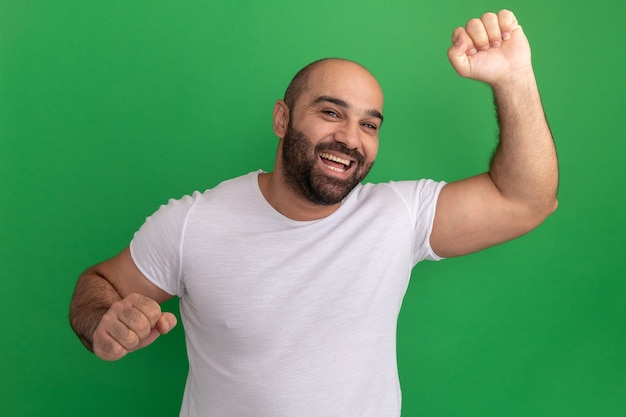 Uomo barbuto in maglietta bianca felice ed eccitato alzando i pugni in piedi sopra la parete verde