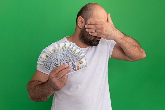 Uomo barbuto in maglietta bianca che tiene gli occhi che coprono i contanti con la mano che sta sopra la parete verde
