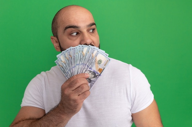 Bearded man in white t-shirt holding cash looking aside worried covering mouth with money standing over green wall