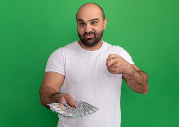 Uomo barbuto in maglietta bianca che tiene contanti che punta con il dito indice sorridente in piedi felice e positivo sopra la parete verde