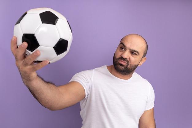 Uomo barbuto in maglietta bianca che tiene il pallone da calcio guardandolo con espressione scettica in piedi sopra il muro viola