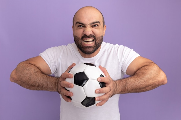 Bearded man in white t-shirt holding soccer ball  with angry face shouting going wild standing over purple wall