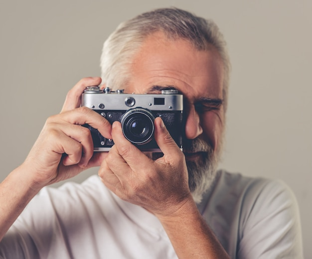 Bearded man in white t-shirt is using a photo camera.