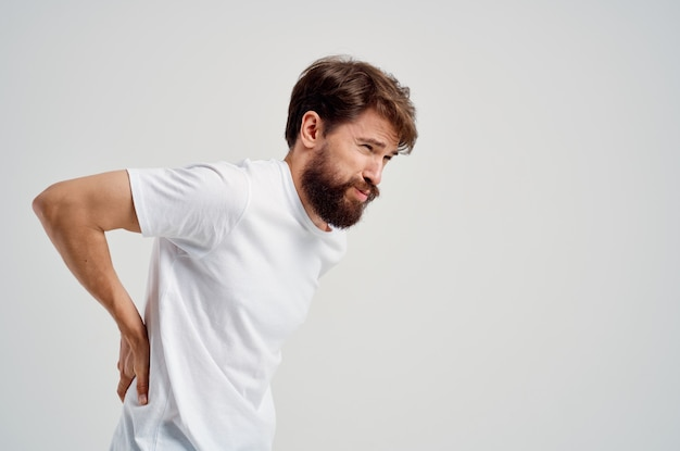 Bearded man in a white t-shirt stress medicine backache light background. high quality photo