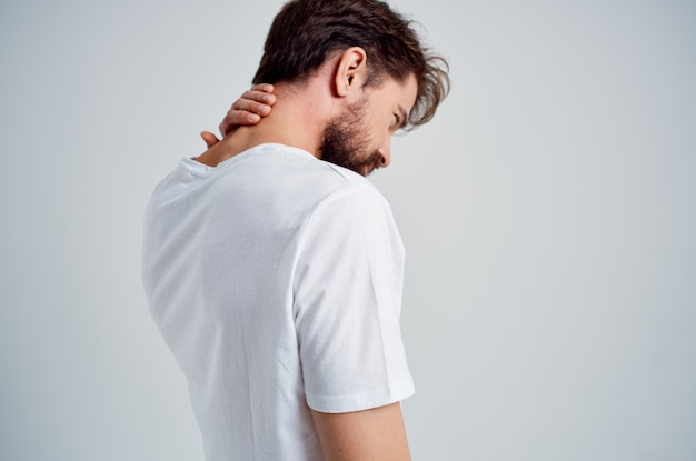 Bearded man in a white t-shirt stress medicine pain in the neck light background. high quality photo