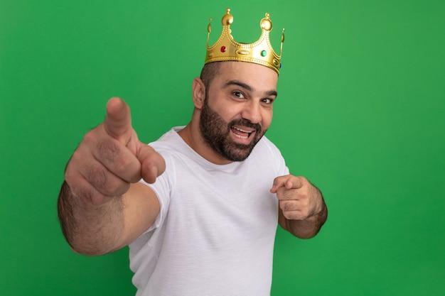 Uomo barbuto in maglietta bianca che indossa corona d'oro felice e positivo che punta con le dita indice in piedi sopra la parete verde