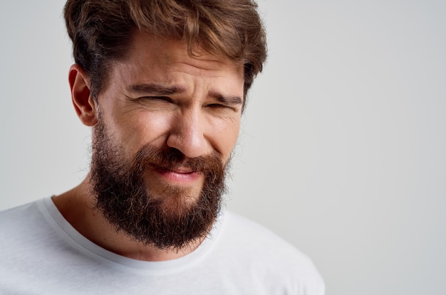 Bearded man in a white tshirt headache migraine problems isolated background