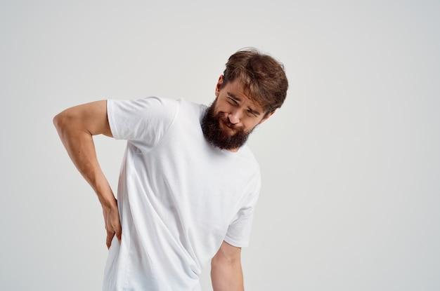 Bearded man in a white tshirt stress medicine backache studio treatment