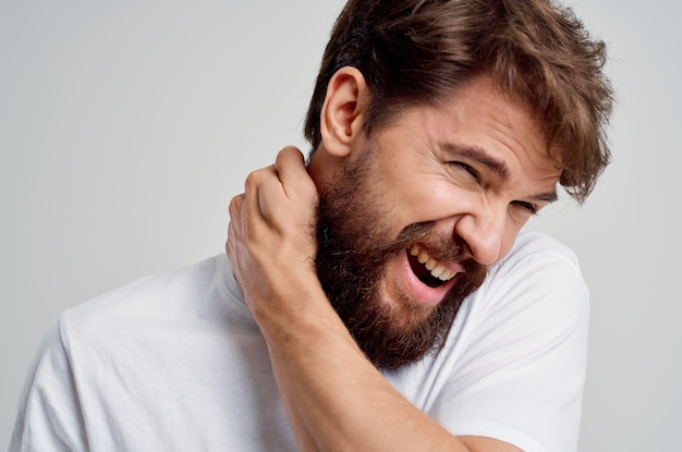 Bearded man in a white tshirt stress medicine pain in the neck isolated background