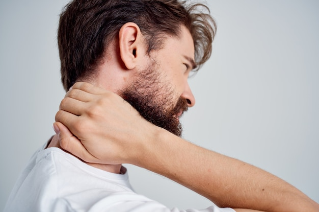 Bearded man in a white tshirt stress medicine pain in the neck light background