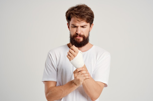 Bearded man in a white tshirt with a bandaged hand posing light background