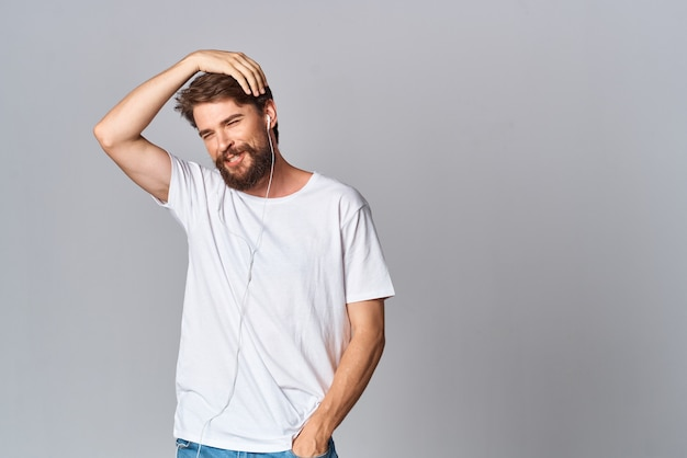 Bearded man in white tshirt with headphones listening to music