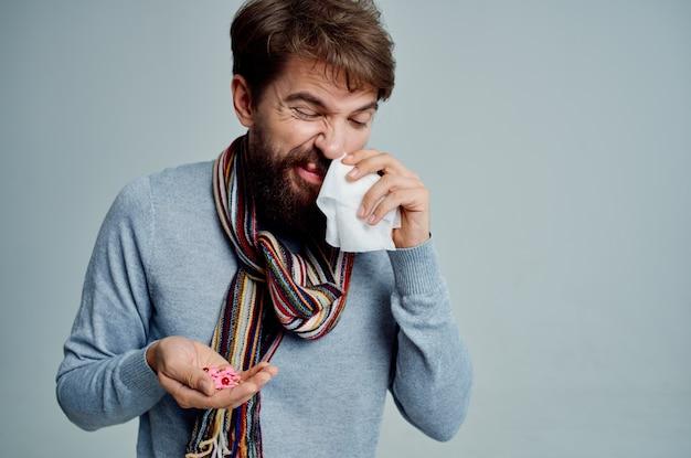ハンカチの健康問題の明るい背景で彼の鼻を拭くひげを生やした男