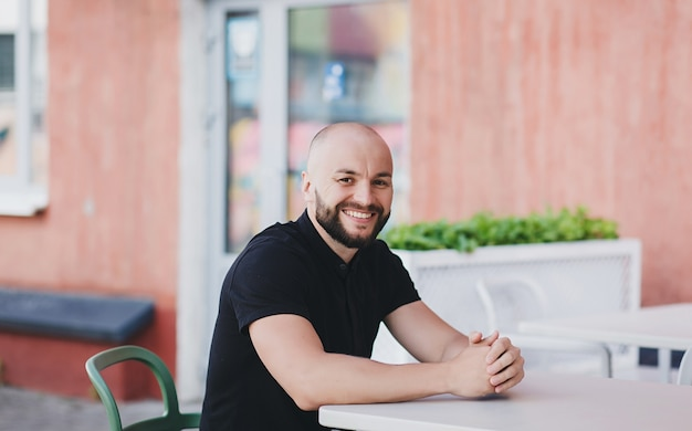 ストリートカフェでtシャツに座って髭を生やしたひげを生やした男が微笑む