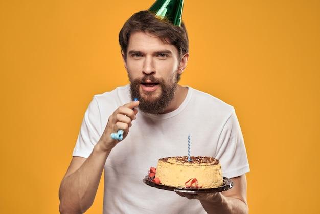 ケーキと彼の誕生日を祝う帽子をかぶったひげを生やした男。