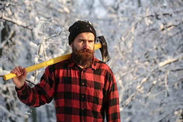 Бородатый мужчина с топориком, лесничество. красивый мужчина, хипстер в заснеженном лесу. дровосек в лесу с топором в зимний день. мужчина держит топор на плече. брутальный бородатый мужчина. мужчина с топором.