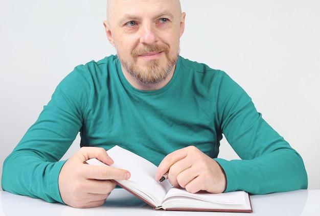 노트북과 펜을 손에 들고 수염 난 남자 생각