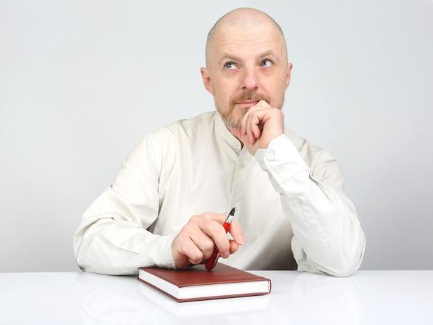 Бородатый мужчина с блокнотом и ручкой в руках думает