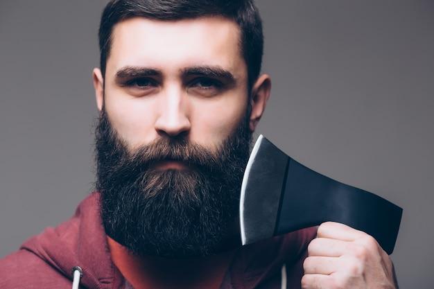 斧を持つひげを生やした男。斧で髪を切る。男性の美容師または理髪店。シャツの残忍な肉屋。森で働く準備ができている木こり。ウッドマンの自信に満ちた残忍さ。ウッドカッターは斧を使用します。