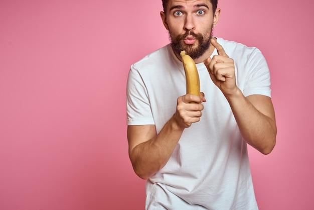 Бородатый мужчина с бананом в руке на розовом фоне веселые эмоции модель