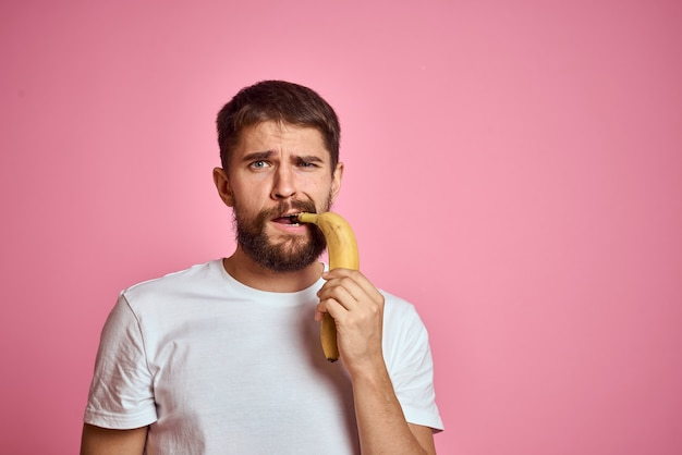 Бородатый мужчина с бананом в руке на розовом