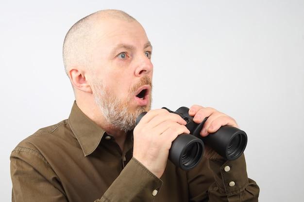 그의 손에 쌍안경을 가진 수염 난 남자는 놀라움과 함께 거리를 본다