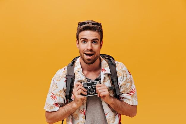 青い目と白いプリントの衣装とオレンジ色の壁にカメラでポーズをとるバックパックのスタイリッシュな髪型のひげを生やした男