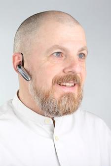 그의 귀에 블루투스와 수염 된 남자