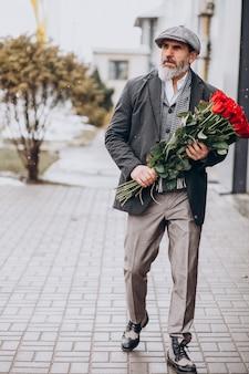 赤いバラの花束を持つひげを生やした男