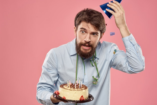 Бородатый мужчина с тортом на розовой стене