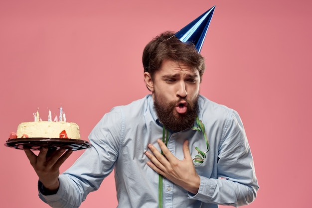 Bearded man with cake on pink background emotions cropped view