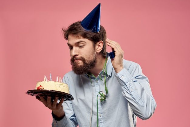 Bearded man with cake on pink wall