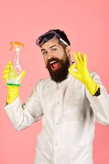 掃除道具を持ったひげを生やした男。クリーニングのコンセプト。クリーニングスプレーで笑顔のひげを生やした男の肖像画。あごひげを生やした男は大丈夫サインを示しています。ハウスキーピング。