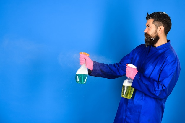 Bearded man with cleaning equipment serious bearded man with cleaning spray cleaning concept
