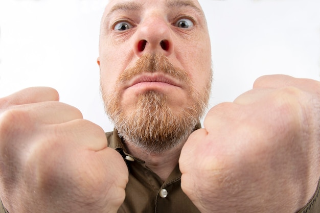 Бородатый мужчина со сжатыми кулаками крупным планом на белом