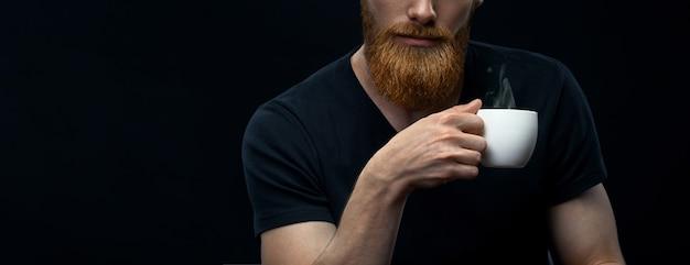 Бородатый мужчина с чашкой горячего кофе или чая