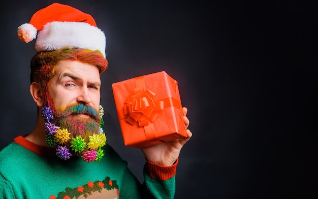 Bearded man with decorated beard in santa claus hat with present gift. merry christmas and happy new year. copy space.