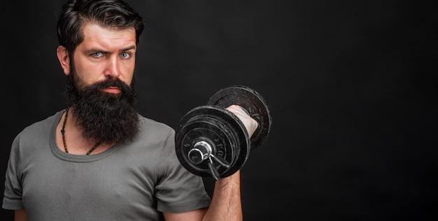 ダンベルでひげを生やした男。ボディービル。スポーツ用品。いい結果。