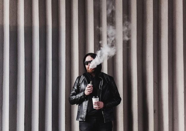 Bearded man with e-cigarette outdoors. stylish guy holding coffee and vaping