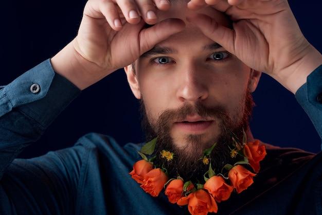 黒のシャツの暗い背景のひげに花を持つひげを生やした男。高品質の写真