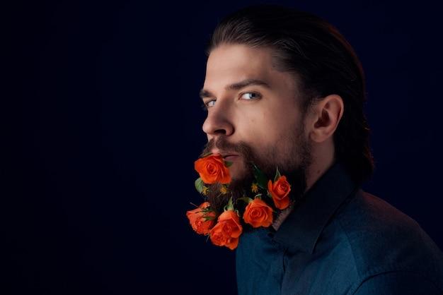 黒いシャツの暗い背景のひげに花を持つひげを生やした男