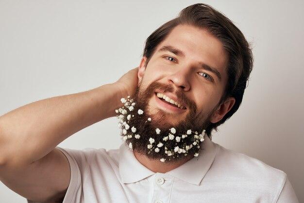 シャツのクローズアップでひげに花を持つひげを生やした男。高品質の写真